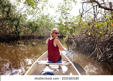 A happy young woman is smiling as she paddles a canoe through the Mangrove Forest in a River in the Florida Everglades.