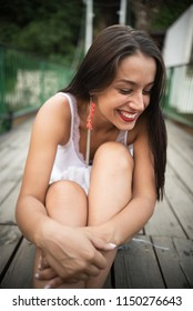happy young woman smiling while sitting on wooden bridge