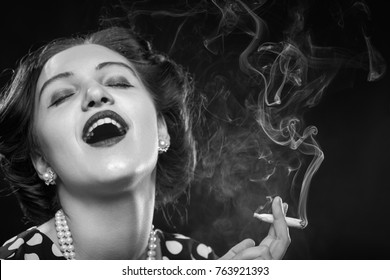 happy young woman smoking joint on black background, monochrome