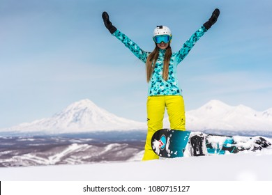 Happy young woman with snowboard in front of volcanos. Russia, Kamchatka peninsula