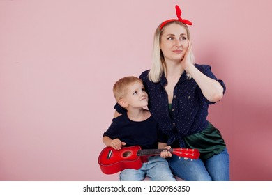 Happy young woman with sons . Portrait on a pink background. Cheerful family