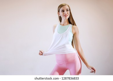 Happy young woman in sports clothing smiling. Muscular fitness model on white background looking away at copy space