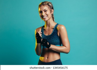 Happy young woman in sports clothing smiling. Muscular fitness model on blue background looking at camera.