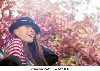 Happy young woman in spring blossom park with soft sunshine, lifestyle, urban fashion