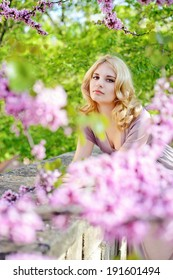 Happy young woman in spring flowers garden