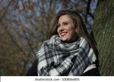 Happy young woman with squares pattern scarf leans on tree trunk on autumn season day in the park. Portrait of beautiful smiling girl on fall fashion style