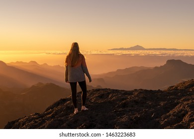 Happy young woman standing and enjoying life at sunset in mountains - gran canaria, spain