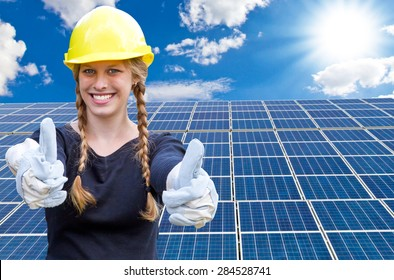 Happy young woman standing in front of solar panels