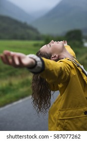 Happy young woman standing in rain with her arms outstretched rejoicing, celebrating and enjoying life