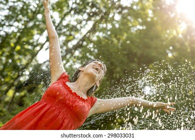 Happy young  woman standing under a spray of water on a hot summer day with her arms outstretched rejoicing, celebrating and enjoying life, leafy green tree background.