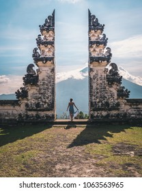 Happy young woman staying in temple gates of heaven in beautiful dress. Perfect travel concept. Lempuyang Luhur temple in Bali, Indonesia.
