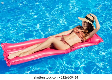 happy young woman in straw hat and bikini  floating on inflatable mattress at swimming pool