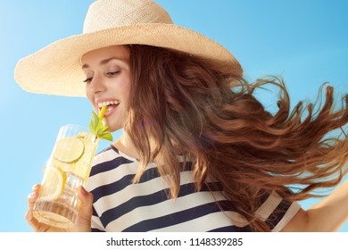 happy young woman in straw hat against blue sky drinking refreshing cocktail