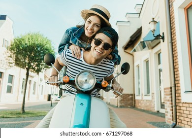 Happy young woman in straw hat and handsome man in sunglases riding scooter together