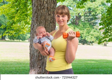 Happy young woman strengthens with dumbbell after childbirth and holds newborn baby