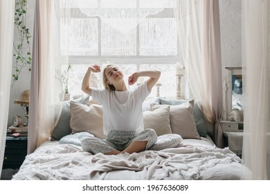 Happy young woman stretching in bed waking up in cozy bedroom with bohemian interior style. Female wearing in comfort pajamas enjoying early morning, resting alone