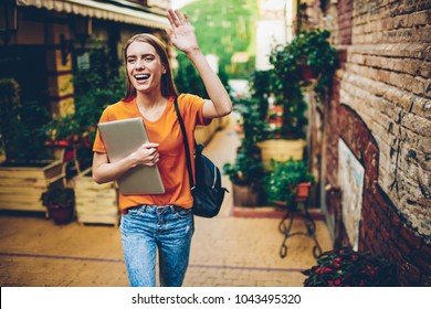 Happy young woman strolling with backpack and laptop and showing hand to friend for meeting.Positive hipster girl dressed in casual outfit holding computer and walking in street of beautiful city