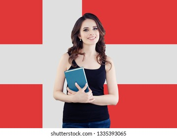 Happy young woman student with book against the Denmark flag background, travel and learn danish language concept