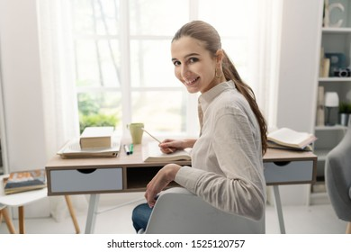 Happy young woman studying at home, she is sitting at desk and smiling at camera