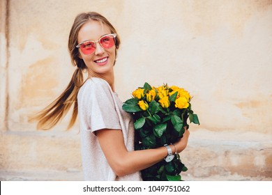 Happy young woman in sunglasses holds a bouquet of yellow roses, posing at camera, wearing t-shirt. Outdoors.