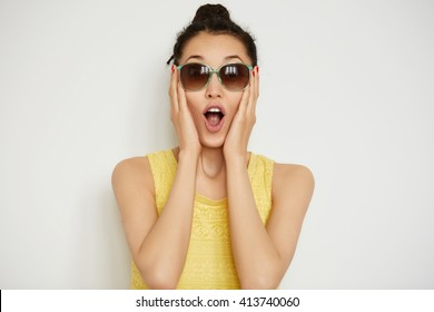 Happy young woman in sunglasses looking surprised at the camera, holding her head in excitement. Close up view of beautiful female posing indoor against white studio background. Body language