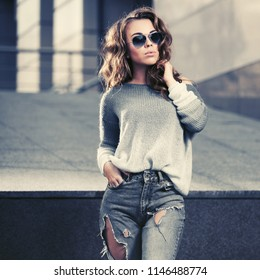 Happy young woman in sunglasses walking in city street Stylish fashion model wearing pullover and ripped jeans