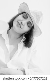 happy young woman in sunhat under sunlight closed eyes relax, monochrome