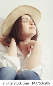 happy young woman in sunhat under sunlight closed eyes relax