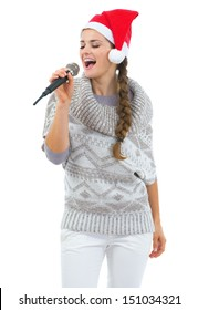 Happy young woman in sweater and christmas hat singing in microphone