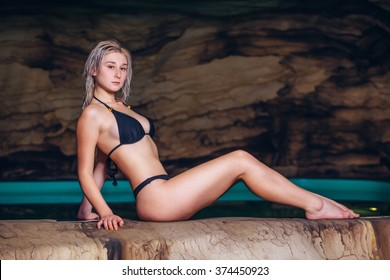 Happy young woman in swimsuit enjoying sitting  cave near the lake
