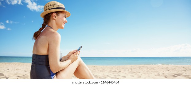 happy young woman in swimsuit with smartphone looking into the distance on the seacoast