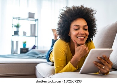 Happy young woman with tablet pc laying on sofa. Young happy woman lie down on bed and playing smart tablet at home. Beautiful young black women using tablet computer