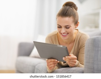 Happy young woman with tablet pc laying on sofa