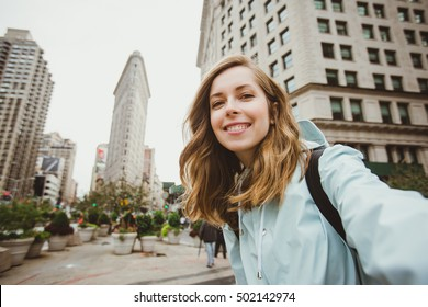 Happy young woman takes selfie photo near Flat Iron building in Manhattan, New York. Attractive girl in her 20s takes picture for her blog while travel.