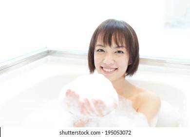 happy young woman taking bubble bath