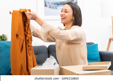 Happy young woman taking clothes out of box after delivery