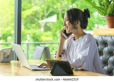 Happy young woman taking on mobile phone. asian woman working at Coffee shop answering a phone call.
