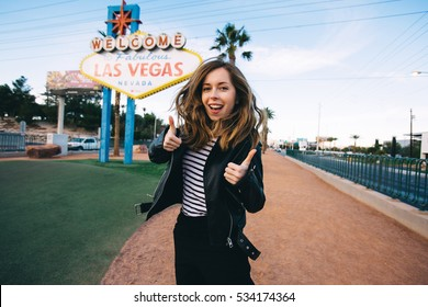 Happy young woman taking photo near Las Vegas Welcome sign. Beautiful girl posing with Las Vegas billboard on the background, Nevada, USA