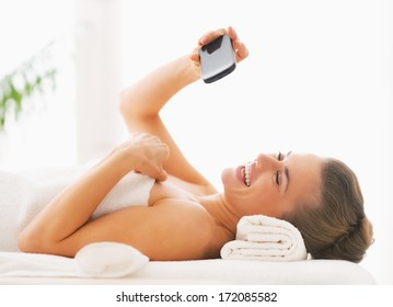 Happy young woman taking self photo while laying on massage table
