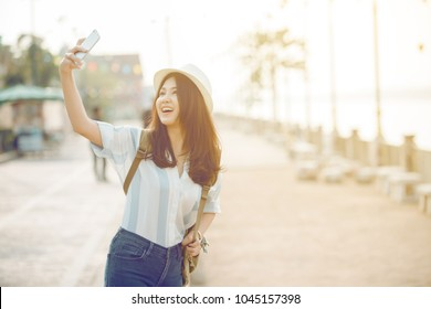 Happy young woman taking selfie on the street