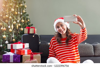 Happy young woman taking selfie over christmas tree