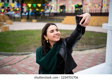 Happy young woman taking selfie. Woman taking selfie photo with a smarphone in the city.