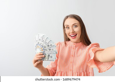 Happy young woman taking selfie with money on light background
