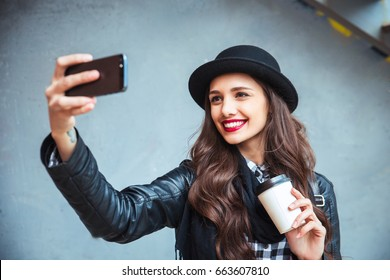 Happy young woman taking selfie. Woman taking selfie photo with a smarphone in the city