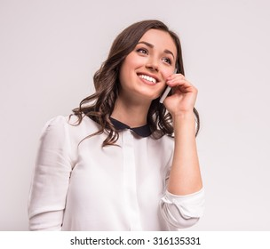 Happy young woman is talking by phone on white background.
