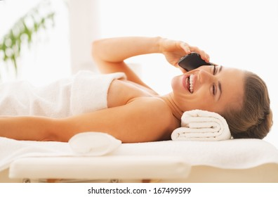 Happy young woman talking cell phone while laying on massage table