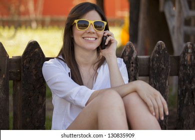 Happy young woman talking to a friend on the phone