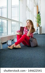 Happy Young woman is talking on mobile phone in the airport