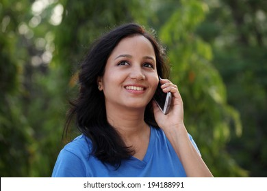 Happy young woman talking on mobile phone at outdoors