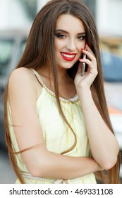 Happy young woman talking on mobile phone at city street lifestyle portrait. Smiling girl with cellphone hearing good news. Pretty lady calling phone outdoor. Soft focus